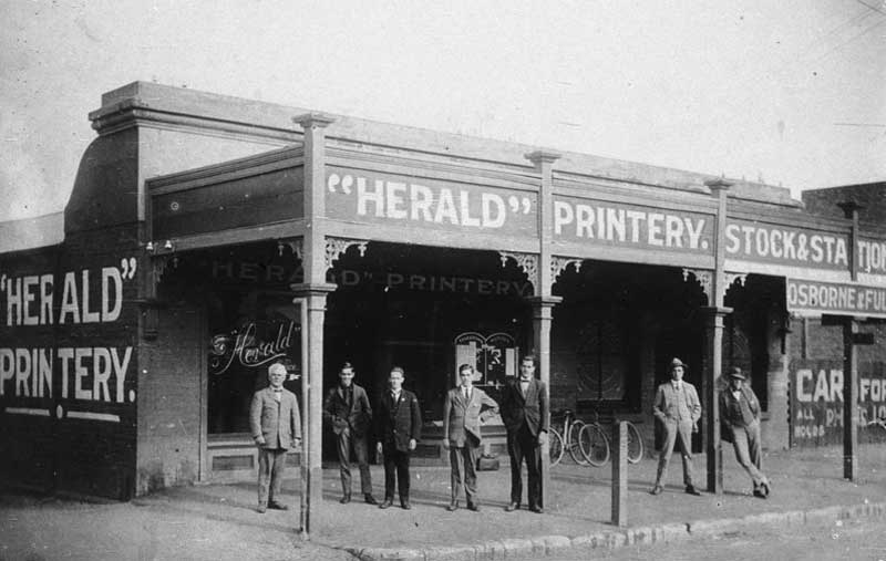"WH Pinkstone, on left, was the second Editor of the ""Herald"", 1916-1950. Printery located in Wallendoon Street, Cootamundra. The Post Office was across the lane on the left, n.d. Image: NSW State Library collection. Reproduction: Peter de Waal"